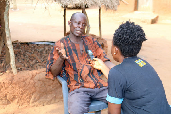 A journalist interviews a farmer who grow OFSP.